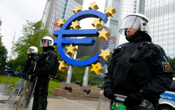 """Riot police stand near the euro sign in front of the European Central Bank headquarters during an anti-capitalist """"Blockupy"""" demonstration in Frankfurt"""
