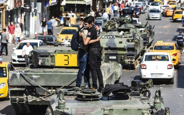 "Turkish police officer (R) embrace a man on a tank after the military position was taken over at the Anatolian side at Uskudar in Istanbul on July 16, 2016. President Recep Tayyip Erdogan urged Turks to remain on the streets on July 16, 2016, as his forces regained control after a spectacular coup bid by discontented soldiers that claimed more than 250 lives. Describing the attempted coup as a ""black stain"" on Turkey's democracy, Yildirim said that 161 people had been killed in the night of violence and 1,440 wounded. / AFP PHOTO / BULENT KILIC"