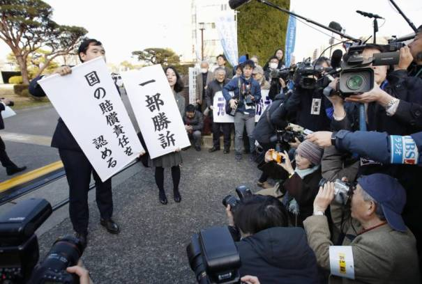 Supporters of plaintiffs seeking compensation for Fukushima evacuees unfurl banners in front of the Maebashi District Court in Gunma Prefecture announcing the court's decision Friday. | KYODO